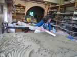 Claudia Bruhin making a big clay slab by pounding and paddling clay pieces