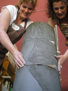 making of a freestanding clay coloumn, showing how to ceramicists add elements on top of each other