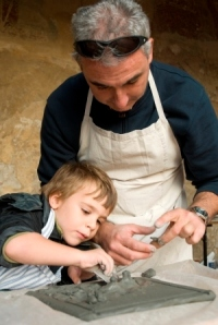 K 12 student working on a clay tile