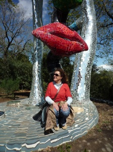 Angeliki Papadopoulou sitting on a ceramic sculpture by Nikki de Saint Phalle