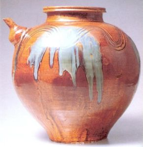 Beautyful example of  a large, found pitcher with orange glazing with  splashed on grey glaze.