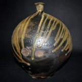 round pot with dark glaze and lighter, running glaze on top. Wood fired by Jeff Shapiro